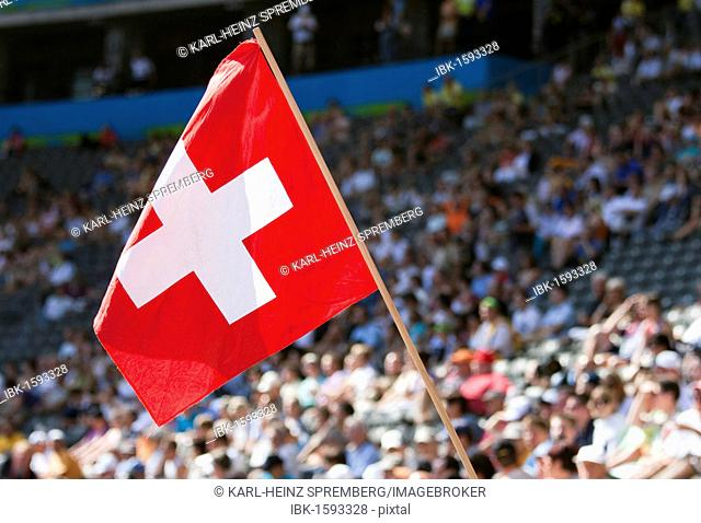 Swiss fan waving the national flag at a sports event