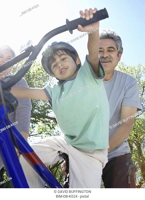 Hispanic grandparents helping grandson ride bicycle