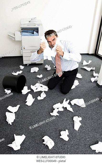 Businessman kneeling in despair, tearing sheets of paper