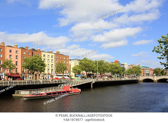 Temple Bar, Dublin, Republic of Ireland, Eire, Europe  View across the River Liffey to Batchelor's Walk with cruise boat moored by jetty