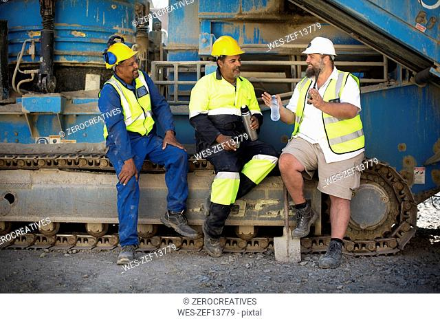 Colleague workers at quarry sitting on machine, taking a break
