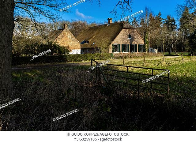 Bilthoven, Netherlands. Traditional Farmhouse and Stable bordering a green meadow on a sunny friday morning