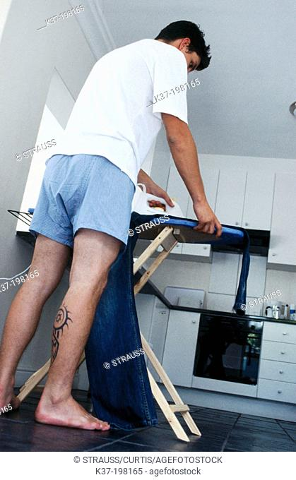 Tattooed man ironing his jeans