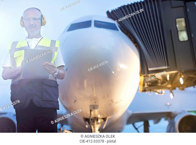 Portrait air traffic controller with clipboard in front of airplane on airport tarmac