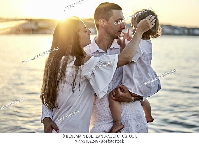 family enjoying togetherness, love, bonding, parenthood, sunset. In Chersonissos, Crete, Greece