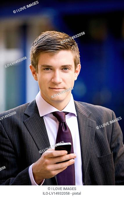 A businessman holding a mobile phone