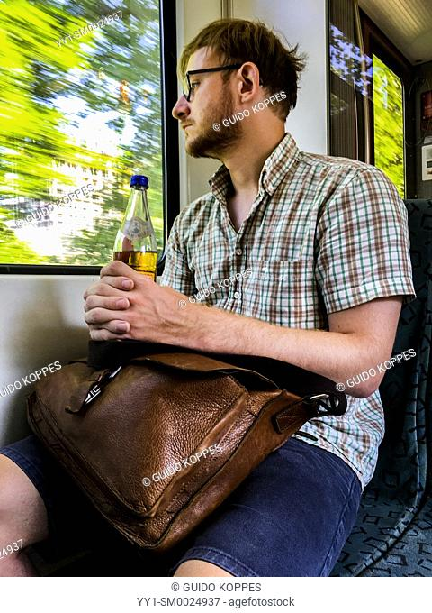 Berlin, Germany. Male S-Bahn passenger and commuter wearing glasses and holding his leather bag, looking out the window when commuting home after work