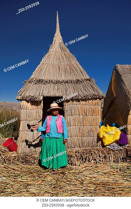 Young Aymara women in front her Totora reed house at Uros Islands, Lake Titicaca, Puno Region, Peru, South America