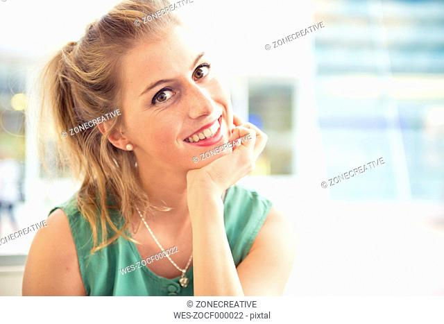 Portrait of smiling blond woman at outdoor cafe