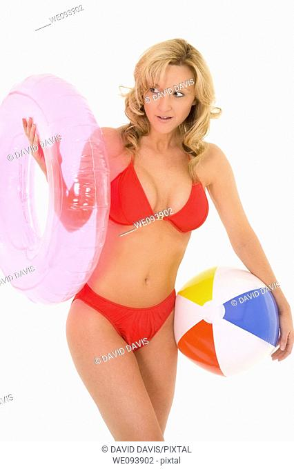 Caucasian woman standing on a white background in a swimsuit holding a beach toy and smiling