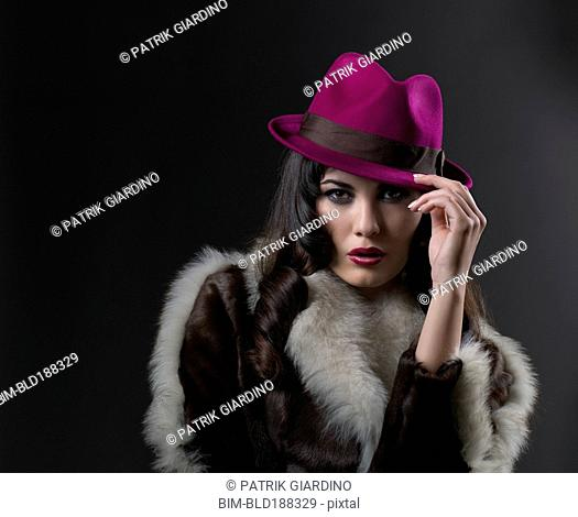 Mixed Race woman wearing hat and fur coat