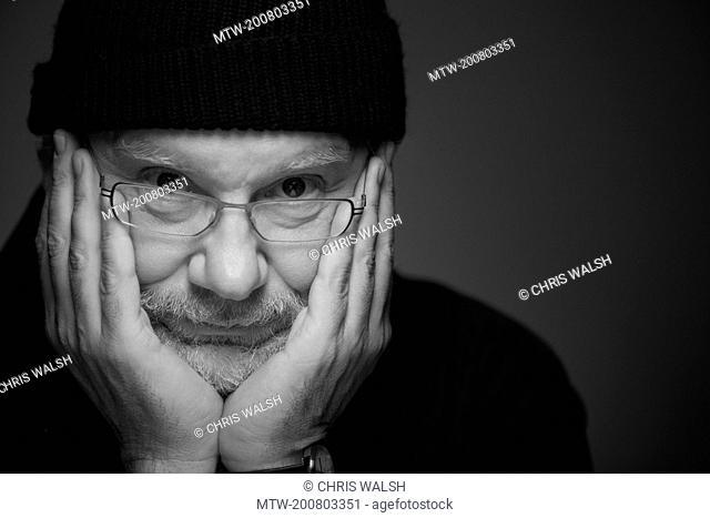 Black and white portrait man head in hands sad