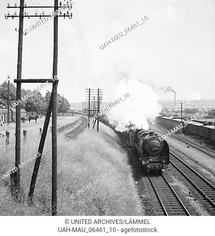 Ein Güterzug, gezogen von einer Dampflokomotive der Baureihe 44, durchfährt einen kleinen Bahnhof, Deutschland 1930er Jahre