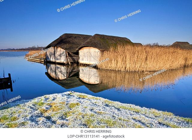 England, Norfolk, Hickling Broad. Boathouses at Hickling Broad on a frosty winter morning