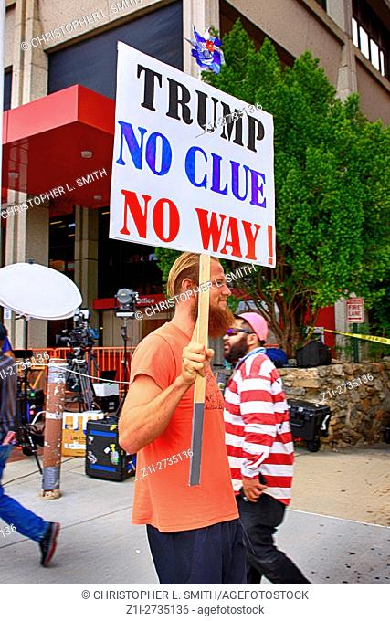 Man holding an anti-Donald Trump banner at a Donald Trump convention in Asheville, NC