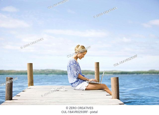Woman working on her notebook lake-side