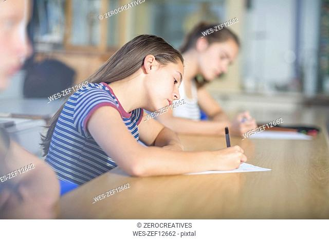 Female students writing during class test