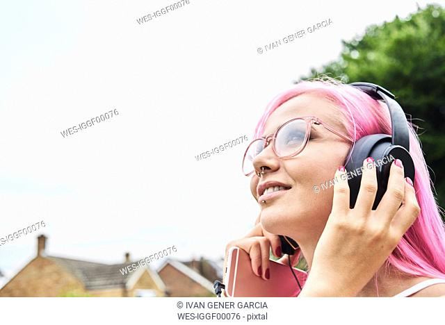 Young woman with pink hair listening to music outdoors