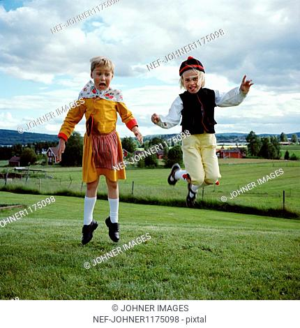 Boy and girl in traditional clothing, jumping