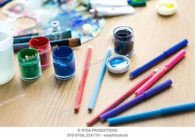 gouache colors, felt tip pens and pencils on table