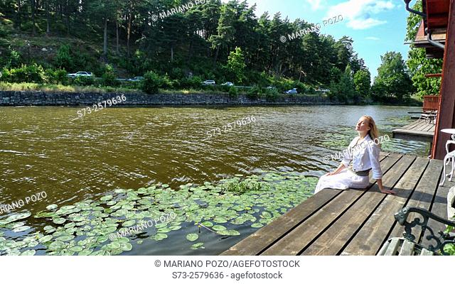 Woman sitting in the Porvoonjoki river in Porvoo, Finland