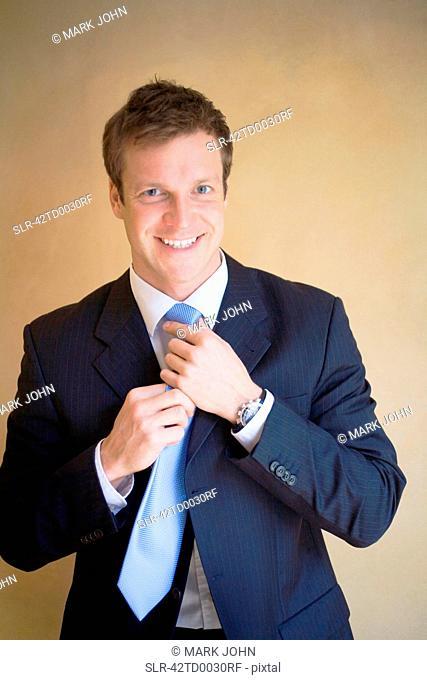 Smiling businessman adjusting his tie