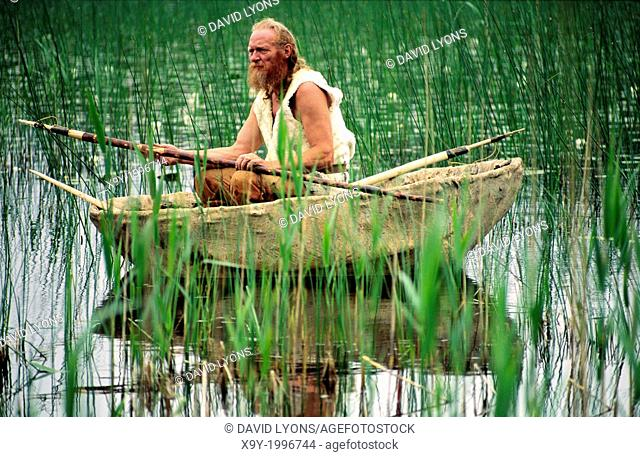 Neolithic re-enactment. Stone Age man holding fish spear in animal hide coracle boat on reed shore lake. Kilmartin, Scotland, UK