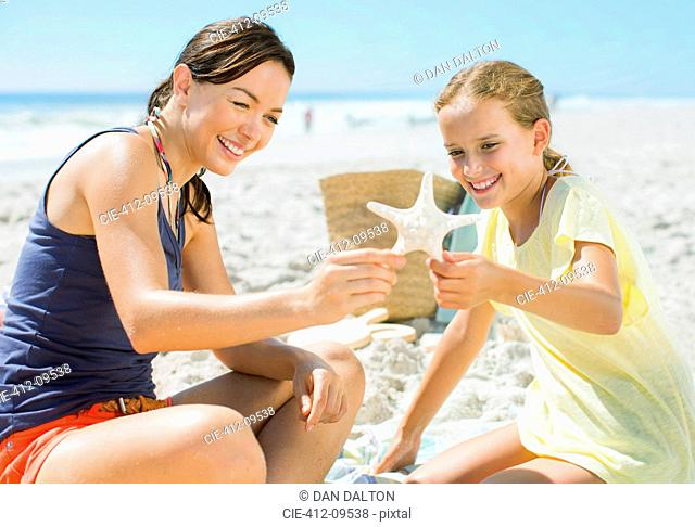 Mother and daughter examining starfish on beach