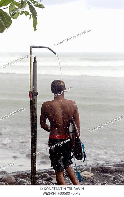 Indonesia, Bali, surfer taking a shower in rain