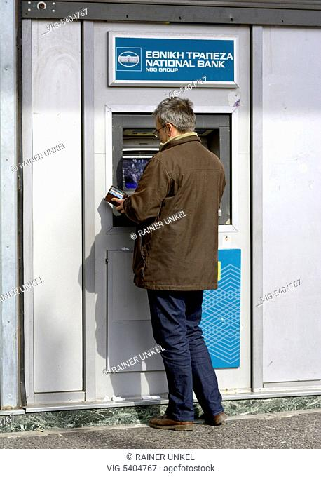 GRC , GREECE : A man taking money from an ATM cash machine of National Bank in Athens , 08.02.2016 - Athens, Attica, Greece, 08/02/2016