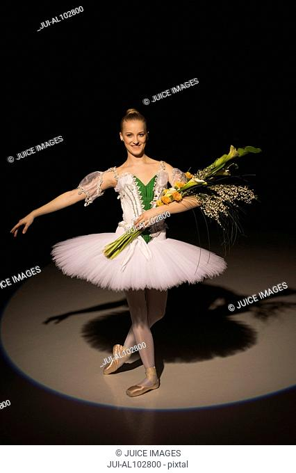 A young ballerina taking curtain call on stage in the spotlight