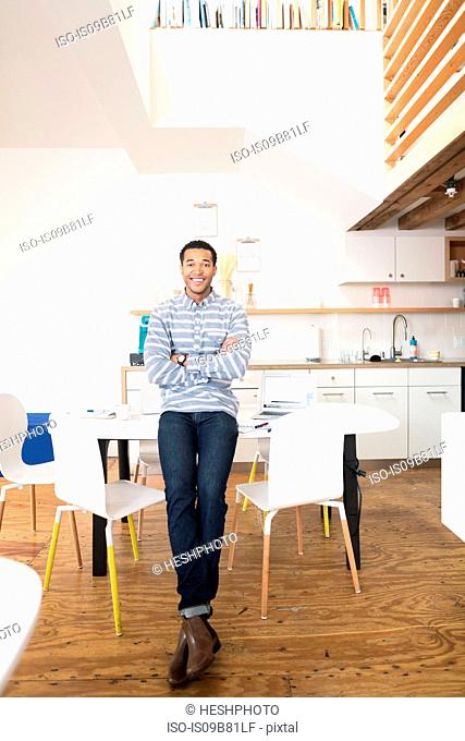 Portrait of cool young businessman in office kitchen