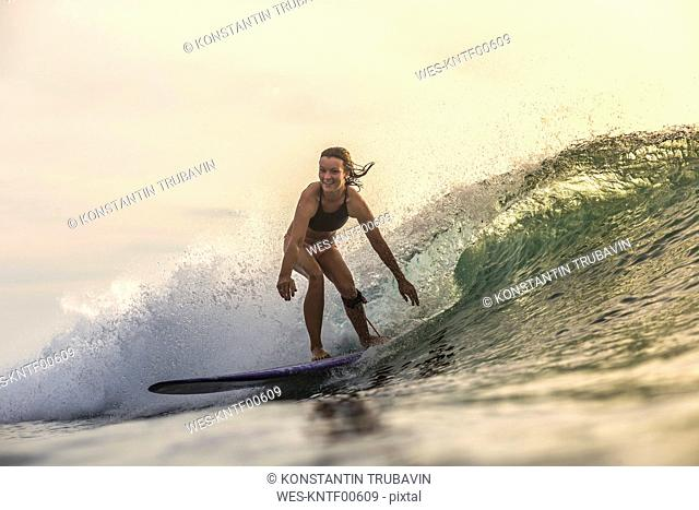 Indonesia, Bali, woman surfing at sunset