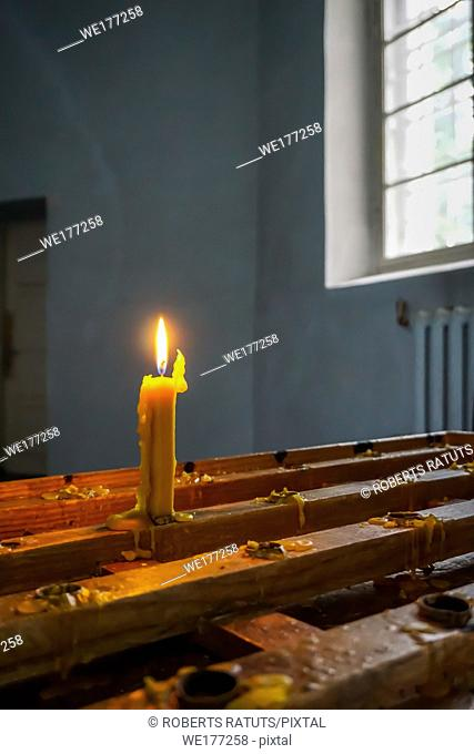 Burning candle at Koknese Evangelical Lutheran Church. Evangelic Lutheran Church in Koknese, Latvia. Interior of Koknese church