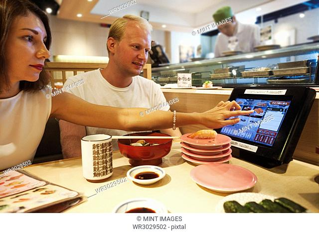 Young man and woman sitting at a table in an Asian Fast Food restaurant, eating sushi, looking at touch screen on their table