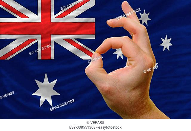 man showing excellence or ok gesture in front of complete wavy australia national flag of symbolizing best quality, positivity and succes