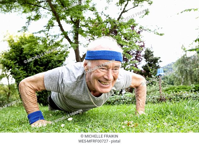 Senior man doing pushups for fitness training in garden