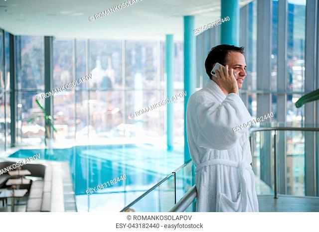 Man use the cellphone at luxury hotel spa in the near the swimming pool