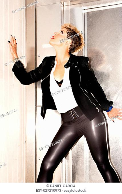 Fashionable woman in seductive position. Urban fashion photography. Vertical image
