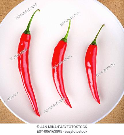 Closeup of three fresh raw red hot chili peppers on plate
