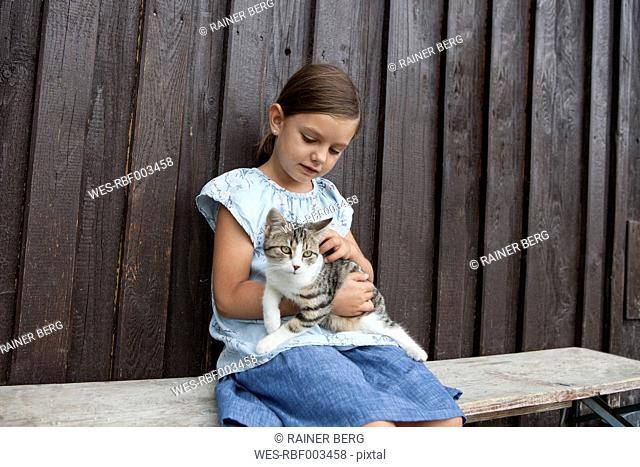 Girl with cat sitting on bench