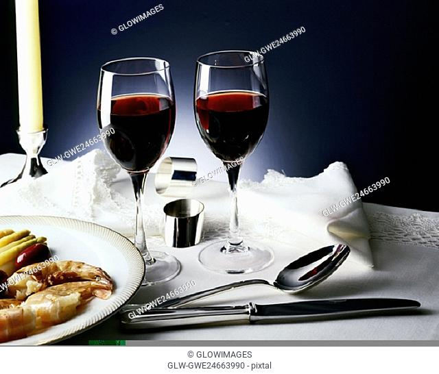 Two glasses of wine beside a plate of prawns