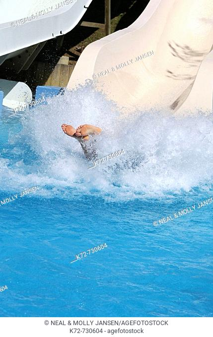 Hitting the water at the end of a long water slid at a waterpark causes a big splash with only a persons feet showing