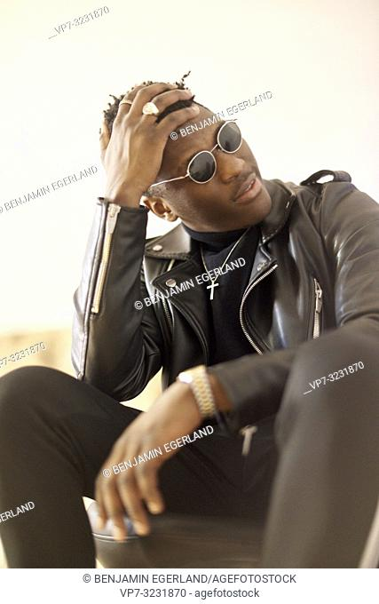 portrait of thoughtful young cool African man leaning head on hand, wearing christian cross necklace and sunglasses indoors in Munich, Germany