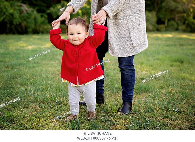Smiling toddler holding her mother's hands in a park
