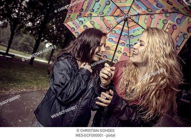 Two happy young women under umbrella in park