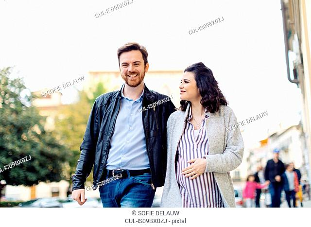 Pregnant couple walking, Florence, Italy
