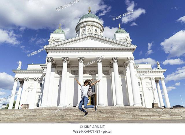 Finland, Helsinki, woman jumping in front of Helsinki Cathedral