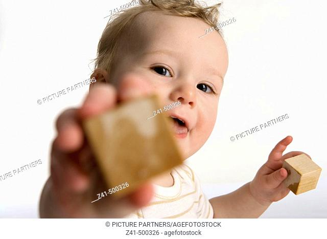 Little boy reaching out with a wooden brick