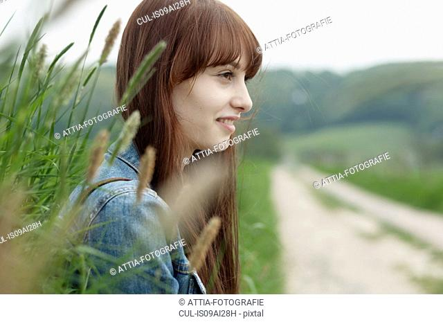 Portrait of young woman next to dirt track
